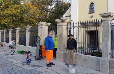 Hausmeister Manfred Paukner und Steinmetz Matthias Gebel bei der Sanierung des historischen Friedhofzauns